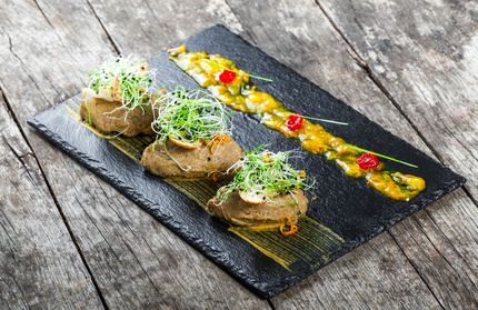 Appetizer from meat pate and onion on stone slate background on rustic table. Top view.